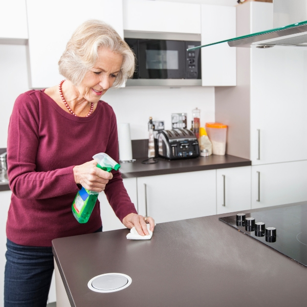 An elderly woman spring cleaning the kitchen countertop