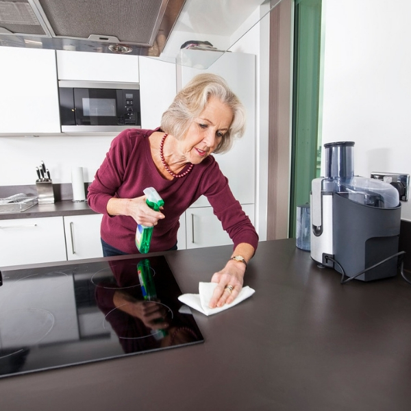 An elderly women using spring cleaning tips and tricks to clean her kitchen