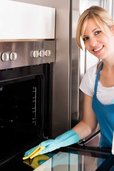 a woman cleaning oven with homemade oven cleaner