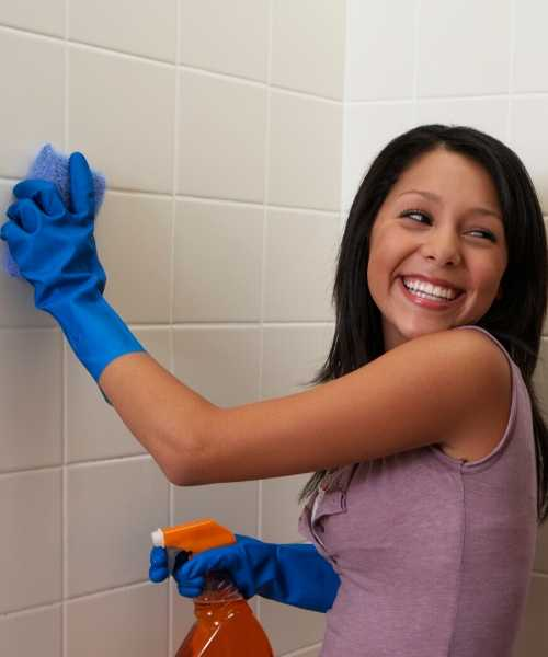 a woman scrubbing bathroom walls