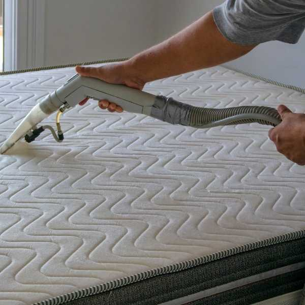 Someone steam cleaning a mattress